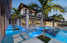Palm trees surround the modern outdoor lounge area of this Naples, Florida, home. A heated swimming pool features sleek steppingstones, while multiple covered outdoor seating areas offer comfortable spots for hanging with family and friends.