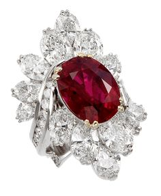 Platinum and 18 karat yellow gold ruby and diamond cluster ring containing one vibrant oval ruby weighing 11.08 carats, fourteen oval diamonds weighing a total of 10.64 carats, with round and baguette diamonds weighing approximately 2.25 carats. l Black, Starr & Frost