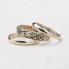 Delicate by design, this set of three sterling silver stacking rings shines with two smooth bands and one hand-carved floral band.