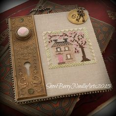 An antique door plate became the inspiration for the finish on this Spring house cross stitch design.