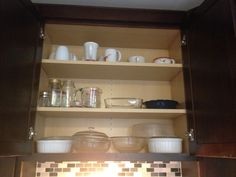 cabinet above the sink which has bakeware, recycled glassware and a bunch of mugs we never use. I guess they are there in case we ever have 50 people over for coffee. #kitchncure