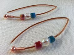 "Glass fired Czech blass cylinders of medium blue and salmon pink arranged around a clear acrylic bead to create a simple and sophisticated look. I like wearing these ""pinched"" where I make the two ends meet each other while I wear them. They will spring back fairly nicely when you remove them from your ears. To each our own!     Finished size: 1 3/4 inches long    Features  • Ear wire stoppers recommended & included  • Gift box of colorful turquoise included with instructions for maintaining…"