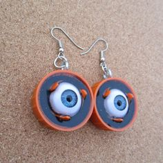 Orange doll eye - upcycled bottle cap earringsrange you glad you clicked on this listing???  I made these freaky little earrings with a pair orange plastic bottle caps that measure 1 inch in diameter. Inside a pair of blue doll eyes, are cast in resin over a film of fine black glitter. (These eyes do not blink.)   Earring wires are surgical steel.   Please visit my shop for other peculiar items!