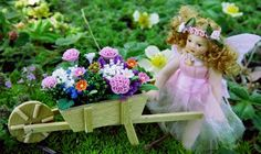 A lovely little fairy wheels a little wheelbarrow full of tiny flowers through the fairy garden.