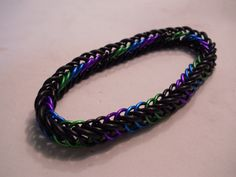 127.  Purple, Green, Blue, and black anodized aluminum with EPDM rubber rings. Slightly stretchy half Persian pattern bracelet. $20