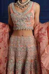 Crafted with love. This outfit is classically designed to make your memorable day beautiful as it should be. The peachy blouse is emphasized with intricate embroidery, handcrafted bootis adorned with silver embellishment finished with dangling pearls all around the edges. Compliment the look with flared lehenga which is decorated with silver kora, dabka, tilla and […] The post Peach Lehenga Blouse Frilled Dupatta appeared first on Latest Pakistani Fashion 2020 - Formal Wear - Anarkali - Pa
