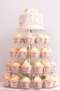 The silhouette of a bride and groom are the perfect addition to this cake perched atop tiers of cupcakes.