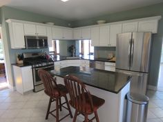 Sage green kitchen with dark green granite counter tops. White tile with white cabinets. All new stainless steel appliances. The kitchen has large bar openings to the sunroom which provide panoramic river views from the kitchen sink.