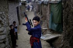 An Afghan refugee boy poses with a plastic rifle as he and other children celebrate the first day of the Eid al-Fitr festival, which marks the end of the Muslim fasting month of Ramadan, in a slum on the outskirts of Islamabad, Pakistan. Pictures Of The Week, Cool Pictures, Cool Photos, My Photos, Islamabad Pakistan, Indus Valley Civilization, Eid Al Fitr, War Photography, Childhood