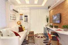 Decoração de salas pequenas - Sala de estar com sofá branco e painel de madeira.