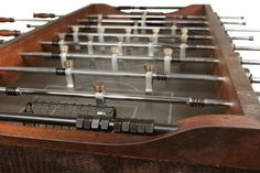 This modern industrial foosball table features a reclaimed hardwood frame in a rich burnt umber finish, handmade aluminum players and beautiful stone playing surface atop a sleek, cast iron base. Foosball Table by Nuevo - Art Van Furniture