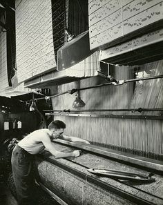 A weaver adjusts a Jacquard loom/Corbis. If you look at the top of the picture you'll see the holes that are punched in cards. Those are the patterns.