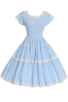 Blue 50's Mexican Patio Dress You can twirl all night in this fun, blue cotton vintage patio dress! This Mexican dress has a side metal zipper and pretty silver and white trim. The dress no longer has