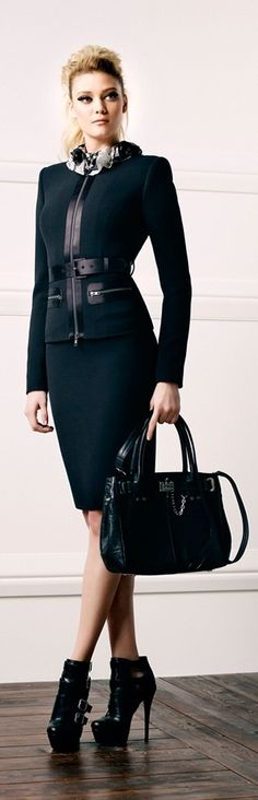Designation of Status: the way the model poses shows she can hold her own and be a boss or at least looks like she is in a higher rank of work because of her suit, bag, and shoes. She's wearing a professional suit and is not so exposed as opposed to sexual enhancement. It shows she's present to talk business.