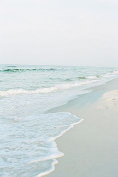 A light gray-blue sky, white sand beach, pale aqua water edged in seafoam || Nature at her best