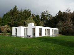 """Residential Architecture: Kerry House by Carson and Crushell Architects: """"..This project is a major reworking of a dilapidated 1960′s bungalow overlooking Kenmare River, Kenmare, Ireland. The structure was wrapped in a thick insulated render lining with high performance glazing fitted flush into existing and newly made openings. All internal rooms were reorganised, improving relationships between the bedrooms and their new en-suites and the relocated kitchen, dining room and central courtyard..."""