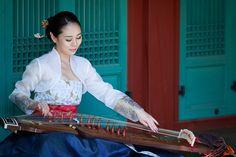 A Korean woman wearing a traditional Hanbok, playing the Gayageum.