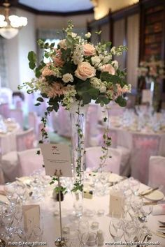 Tall Vase Table Display Tall vase with pale blush pink roses, white stocks and white hydrangea at The Elvetham Wedding flowers by Exclusively Weddings Photo by Adam Jefferson