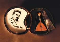 THE V. V. ANDREEV COMPOSITION by Mykola Syadrisky:  One half of a poppy seed has a flosted glass on which a portrait of the Russian composer V. V. Andreev is engraved. The other half contains a case which is open to show it contains a balalaika replika, consisting of 40 elements.