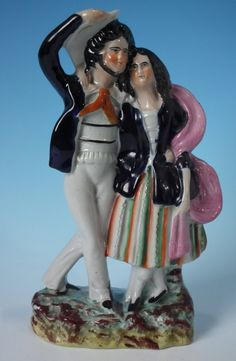 Xmas gift:: Staffordshire figure which features a sailor with his arm around his lass, stood on a shaped base. Multi-coloured with underglaze blue version. Dull gilt embellishment. Flatback, decorated only to the front. Vent hole to the reverse. Book reference not found.