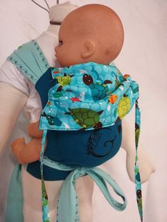 "Doll Carrier "" Gaia-am ""  made with our LAGOON and EMERALD fabrics - 100 % organic cotton broken twill - weaved and dyed in France for "" Colimacon et cie "" - available by the meter on www.echarpe-colimacon.com https://www.facebook.com/page.gaia.am/photos/o.136330169713991/299624266912112/?type=3"