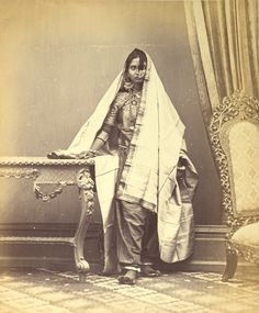 Portrait of a Muslim girl from Sindh, showing method of wearing ear and nose rings, necklace and anklets  Creator:  Photographer : Michie and Company  pany  |  Date: [1870] ; c. 1870Full-length standing studio portrait of a Muslim girl from Karachi in Sind, Pakistan, taken by Michie and Company in c. 1870, from the Archaeological Survey of India Collections. This is one of a series of photographs commissioned by the Government of India in the 19th century, in order to gather information…
