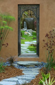 A mirror hung on a wall creates an illusion for a larger space.  great idea for a small garden