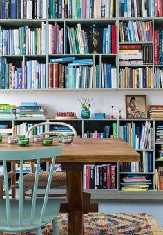 To store bogreoler fyldt op af farverige bøger i spisestuen