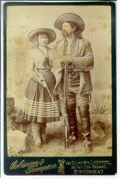 Strong portrait of a pair of Wild West performers, attired in western garb, and both holding rifles. Taken in England (Robinson & Thompson, Birkenhead photographer's imprint), as the majority of American Wild West troupes toured Europe, most notably Buffalo Bill Cody's shows.