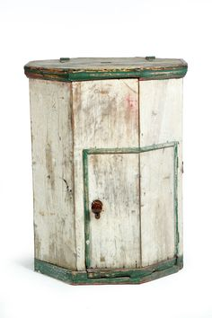 "EARLY ICEBOX. American, late 19th century, wood and zinc. Octagonal form with a lift lid to access the cold compartment and a lower door to access the ice storage. Old white and green paint. Imperfections. 39""h. 32""d."
