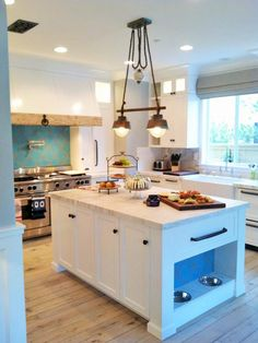 A large island is the centerpiece of the kitchen, providing extra counter space for preparing meals. With two dogs and a cat, it was also important to incorporate their needs, so food and water bowls are built into the end of the island.