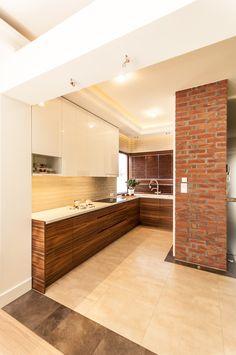 Kuchnia z elementami cegły i drewna, otwarta na salon.