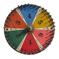1stdibs | Spinning Gaming Wheel SOLD. 20th century MATERIALS: Metal pegs and finial screwed onto graphic painted plywood. CONDITION: Good LENGTH: 14 in. (36 cm) DEPTH: 2.5 in. (6 cm) HEIGHT: 14 in. (36 cm) DEALER LOCATION: New York City, NY