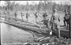 "8 August 1941, 14:55. Finnish troops cross a partially completed bridge. ""On the opposite shore our boys have become entangled in a firefight with Ivan. Stray bullets fly whining over the bridgemakers' heads."""