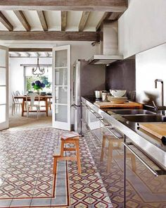 Rustic beams, cement tile flor and a long bank of stainless base cabinets is a very European look.