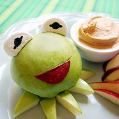 Kermit's Green Apples with Peanut Butter Dip  By Miranda Becker    Print  1 Comment Share  Apples and peanut butter are a classic snack, and an unexpected treat when the apple looks like everyone's favorite frog. Kermit comes alive when you carve a green apple to look like the world famous frog and you add marshmallow eyes and a red apple slice for his mouth. Serve the apple with a tasty peanut butter dip.    You'll need:    For Kermit:    1 green apple  1 red apple  1 marshmallow  Black edible marker  Sharp paring knife  For peanut butter dip:    1/2 cup creamy peanut butter  1/2 cup marshmallow fluff  2 teaspoons lemon juice  Instructions:    1. Slice a green apple in half, from the stem to the end.      2. Place half of the apple on your plate and reserve the other half.    3. Trim two diagonal slices from the tapered end of the apple, making one end of the apple narrower.      4. Use a sharp knife to carve a half moon-shaped smile into the center of the apple.      5. Trim a slice of red apple into a matching half moon shape. Cut away most of the white of the red apple slice so that the skin is easy to bend.      6. You will need to press the red apple slice into the opening in the green apple. Trim the skin until it fits snugly.    7. Cut a marshmallow into 4 quarters. You will use two of the half circles for Kermit's eyes.    8. Use the black edible marker to draw on pupils.    9. Press Kermit's eyes onto the apple. The sticky marshmallow acts like glue, holding the eyes in place.    10. Take your reserved green apple and trim a few triangle shapes. Place these around Kermit's neck, as his ruffle.      11. Mix the peanut butter and marshmallow fluff in a small bowl.    12. Add 2 teaspoons of lemon juice. The lemon juice will help loosen up the peanut butter and marshmallow, giving it a creamy consistency. It will also balance the sweetness of the marshmallow.