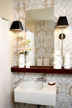 Bathroom vanity. White sink, black wall lamps with skinny poles, wood shelf, rectangle mirror, brown and white wall paper