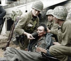 American soldiers give water to a wounded German soldier in Limay, France in 1944.
