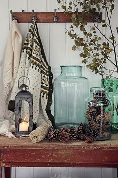 Such a sweet fall to winter vignette filled with the warmth candle light, textiles, nature's elements like pine cones, and lovely giant blue glass jars.