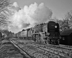 A crisp morning in south Hampshire. A London bound express leaves New Milton headed by a Bulleid light Pacific.  Hampshire, UK. Negative scan.