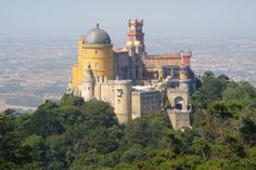 Pena National Palace, Sintra, Portugal. A palace built by King Ferdinand II, it looks like a mash up towers, facades & architectural flourishes from a bunch of different castles. (a medieval European castle complete with ornate parapets next to an Islamic tower dome, diff. colors of purple, red clock tower, a yellow minaret)  Ferdinand wanted the palace to look like an opera.