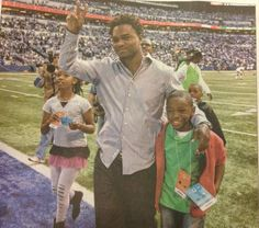 Edgerrin James with two kids involved with his charity, The Edgerrin James Foundation. He created it with the goal of improving the decision making of at-risk children
