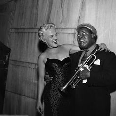 "1954 - Louis Armstrong poses with singer Peggy Lee backstage in 1954. Both guests on the Colgate Comedy Hour's fall TV debut in Hollywood Bowl, they warm up with a backstage duet. Satchmo rendered his version of ""Whiffenpoof Song,"" with special lyrics lampooning bop musicians."