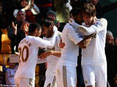 Embrace: Michu is mobbed by his Swansea team-mates