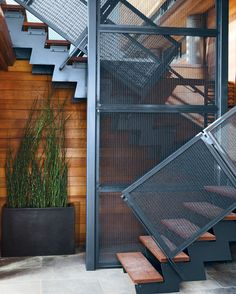 The steel stairwell that connects the garden-level patio with the new living space performs double duty as an anchor attached to the foundation.  Photo by: Mathew Scott