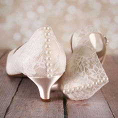 Dress up your trip down the aisle with these 1 3/4 (measured as shown here: http://www.customweddingshoe.com/about-ellie-wren/heel-height-measurement/) ivory kitten heel peep toes, featuring an ivory lace overlay with a silver crystal piece on the toe and a row of ivory pearl #weddingshoes
