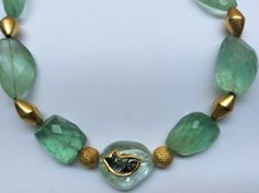 Fluorite tumbles, gold beads and in center, aquamarine tumble carved with a tourmaline's fish setting in a 22 kt. gold.