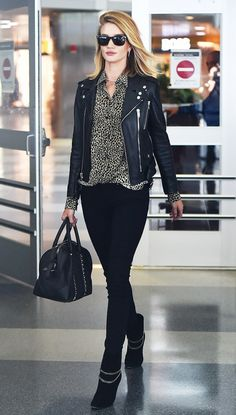 Rosie Huntington-Whiteley wears a leopard print button-down shirt, leather biker jacket, skinny jeans, ankle boots with chain detailing, and a black bowler bag