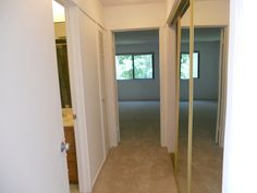 Hall with Large Mirrored Closet that leads to Bathroom & Spacious Bedroom with Brand New Soft Berber Carpeting in a beautiful neutral tone that also is in Bedroom.