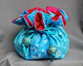 Sweet Sue, Adorable handcrafted Travel Jewelry Bag with hot pink satin lining and 8 storage pouches.  Silk cording with blue and gold filligree beading.